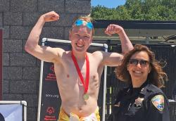 Wyatt Wheetley flexes on the medal stand with a member of law enforcement